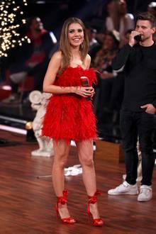 Federleicht moderiert Victoria Swarovski über das Tanzparkett. Sie trägt ein rotes Minikleid mit Federn und setzt damit ihre schlanken, trainierten Beine gekonnt in Szene.