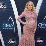 Im November 2018 freut sich Carrie Underwood schon sehr auf ihr Baby. Rundum glücklich zeigt sie sich in einem wundervollen Blumenkleid bei den CMA Awards.