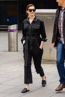 Schauspielerin Anne Hathaway hat den perfekten Airport-Style für sich gefunden: In einem schwarzen Jeans-Overall mit weißen Nähten und bequemen, schwarzen Leder-Schlappen kommt sie am Londoner Flughafen Heathrow an.