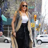 Bei frostigen 10 Grad Außentemperatur wagt sich Jennifer Lopez im April 2019in diesem extravaganten Look und mit nackten Oberarmen auf die New Yorker Straßen. Zu einer Stoffhose mit hohem Bund kombiniert die 49-Jährige ein schlichtes Top, superhohe High Heels und eine knielange Pelz-Weste – bei der es sich hoffentlich um täuschendechten Fake-Fur, also Kunstfell handelt.