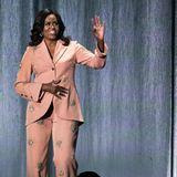 Zu Hosenanzügen scheint bei Michelle Obama sowieso ein Hauch Glitzer zu gehören. Wie gut also, dass das Label Stine Goya ihr dieses Modell maßangefertigt hat und ganz offensichtlich auf ihren geliebten Style eingegangen ist. Überall funkeln hübsche Sonnen aufdem blushfarbenen Stoff.