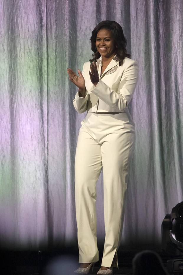 Funkelnde Fashionista: Zum weißen, angesagten Hosenanzug von Acne Studios trägt Michelle Obama spitze Glitzer-Pumps von Jimmy Choo, die perfekt zu ihren Broschen am Revers passen.