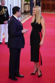 Für ein Event im Weißen Haus wirft sich Ivanka Trump in Schale: Zu einem schlichten, schwarzen Top trägt sie einen schwarzen Rock mit rotem Seitenstreifen. Schwarze Pumps runden den Look ab.