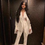 Selena Gomez feiert ein fulminantes Bühnen-Comeback komplett in Weiß. Zu einem klassischen Hosenanzug trägt sie ein bauchfreies Spitzenoberteil.