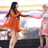 Kacey Musgraves und Baddiewinkle (rechts) tanzen auf der Bühne: Während Kacey auf ein oranges Fransendress setzt, trägt der Internetstar ein buntes Kleidchen mit Blumen.
