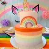 """Die Torte trifft das Thema perfekt: Ihr erster Stock istfarbig gestreift, der zweite mit einem Regenbogen aus Fondant verziert. Besonders witzig: das """"Eins-Horn""""."""
