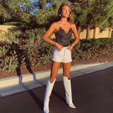 Modelkollegin Lorena Rae setzt ihre langen, gebräunten Beine in weißen Cowboystiefeln in Szene. Dazu trägt sie eine Korsage und Jeansshorts.