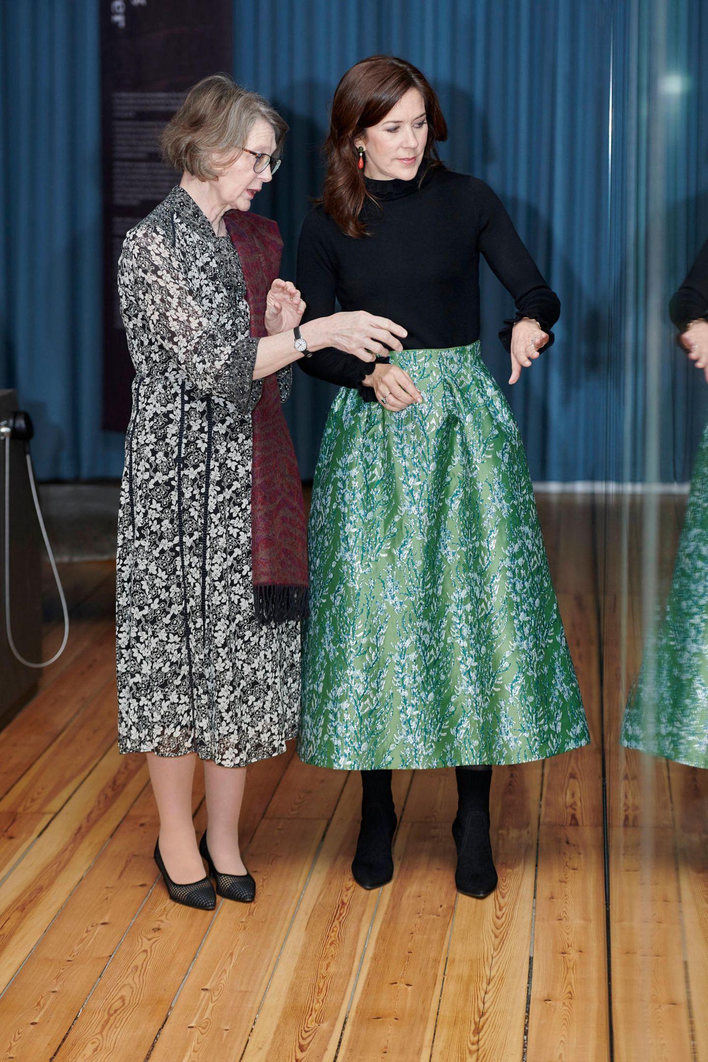 Prinzessin Mary zieht in einem glänzend-grünen Rock mit floralem Muster alle Blicke auf sich. Zu dem It-Piece von H&M kombiniert sie schwarze Stiefeletten und einen schwarzen Rollkragenpullover.
