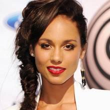 Alicia Keys bringt den Sommer auf den roten Teppich. Ihr Fischgrätenzopf umspielt sanft das Gesicht. Der auffälligeOhrschmuck und die roten Lippen setzen zusätzliche Akzente.