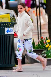 Es ist Suri Cruise! Eingekuschelt in eine weiße Teddy-Jacke genießt sie das oft noch etwas frische Frühlingswetter. Falls sich warme Sonnenstrahlen blicken lassen, ist der Teenie auch bestens vorbereitet: Denn Suri trägt Ballerinas in zartem Rosa und ihre geblümte Lieblingsculotte, mit der sie erst kürzlich gesichtet wurde.