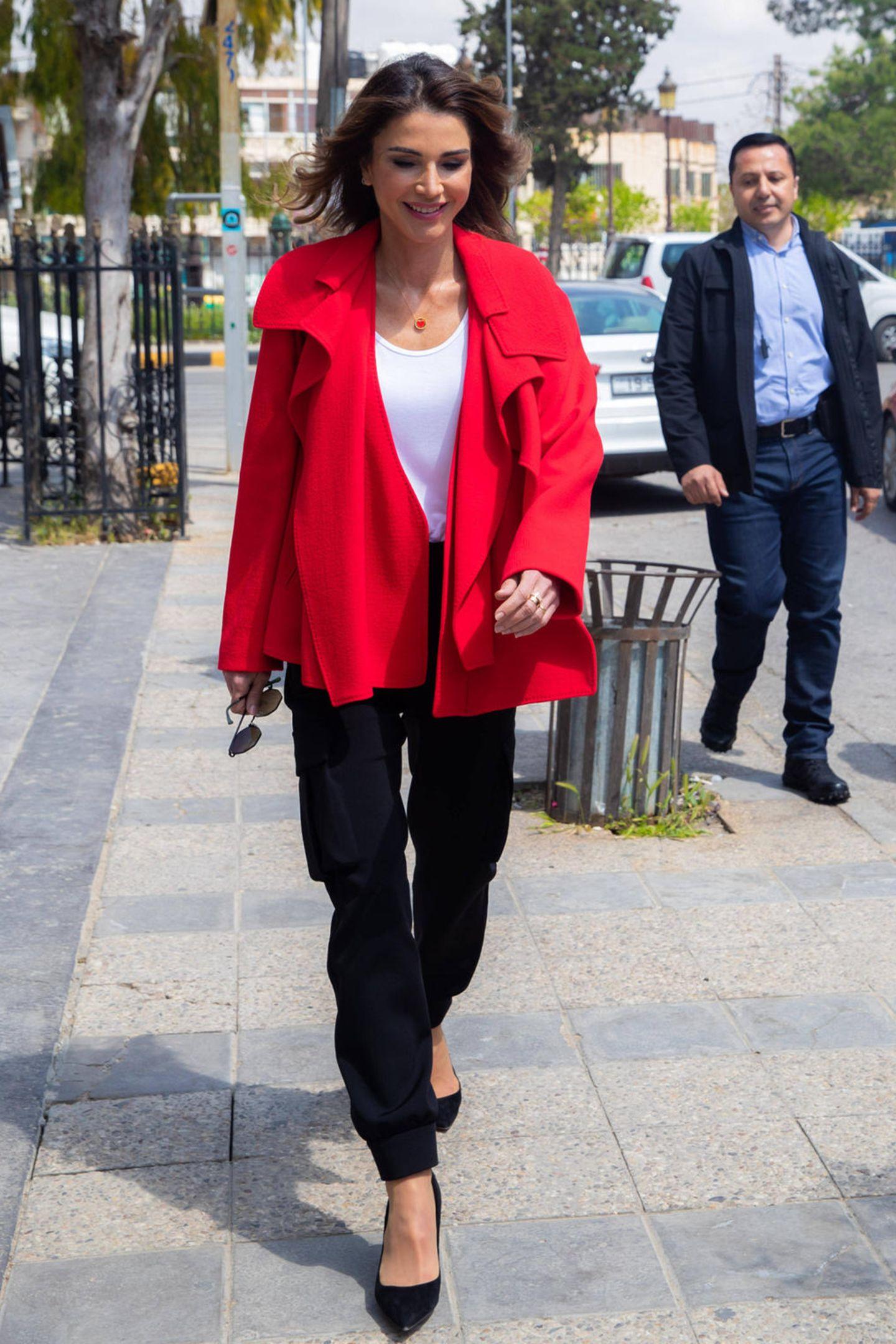 Königin Rania weiß, wie sie ein schlichtes Outfit schnell zum Hingucker werden lassen kann. Zum schwarz-weißen Look zieht sie einfach eine knallrote Jacke an und wählt ein passendes Kettchen.