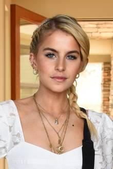 Caro Daur kombiniert eine romantische Flechtfrisur zu ihrem weißen Spitzenkleid. Im Haar sorgen glitzernde Perlen für einen zusätzlcihen Hingucker.