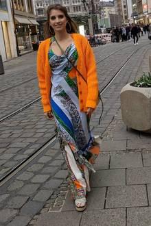 Auch bei diesem Look setzt Cathy Hummels auf Farben. Das bodenlange Print-Kleid steht im starken, materiellenKontrast zur knallorangenen Wolljacke.