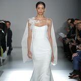 Dieses Brautkleid von Nouvelle Amsale besticht durch zwei hübsche Details. Zum einen ist es die feien Spitze, die sich über die Schulter legt...