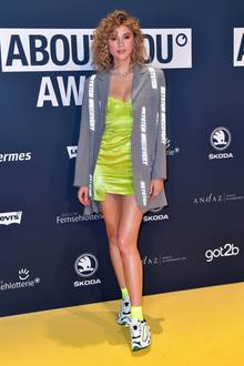 """Model und Influencerin Stefanie Giesinger ist an diesem Abend Jurorin in der Kategorie """"Idol of the Year"""". Sie zeigt sich bei den About You Awards in einem für sie ungewöhnlichen Look. Ihre Haare trägt sie gelockt - statt High-Heels trägt sie Sneaker. Ziemlich sexy ist ihr Minikleid in Neonfarben, dazu kombiniert sie einen grauen Oversize-Blazer."""
