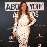 """Comedian Enissa Amani verleiht den About You Award in der Kategorie """"Comedy"""". Auf dem Red Carpet zeigt sie sich in einem weißen Midi-Kleid, das mit viel nackter Haut für Aufsehen sorgt."""