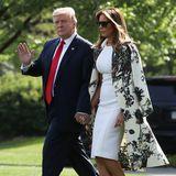 Die First Lady kombiniert zu einem schlichten, weißen Etuikleid einen auffälligen und hochwertigen Mantel. Das Modell stammt vom Label Adam Lippes und ist mit knapp 2.000 Euro ein tolles Investment-Piece. Farblich auf den Mantel abgestimmt wählt Melania orangefarbene Pumps zu diesem Look.