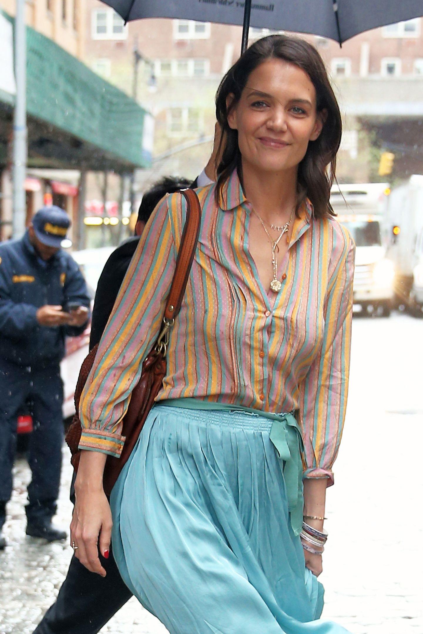 Farblich perfekt auf ihren Rock abgestimmt, kombiniert Katie eine bunt gestreifte Bluse zu ihrem Seidenrock. Ein schönes Detail: Ihre filigranen, goldenen Ketten.