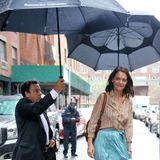 Damit Schauspielerin Katie Holmes trockenen Fußes am Ziel ankommt, wird sie gleich von zwei Schirmträgern begleitet.