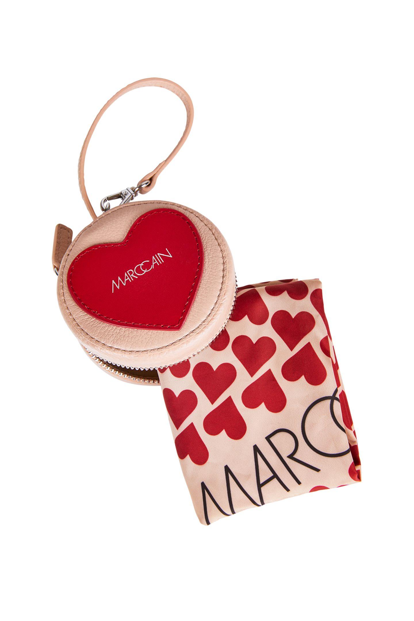 """Gutes tun: Die """"Help Bag"""" von Marc Cain aus geprägtem Leder ist nicht nur das perfekte Präsent zum Muttertag, sondern unterstützt auch noch einen guten Zweck. Die limitierte Tasche kommt in runder Form ineinem Beigeton mit rotem Herz daher. In der Tasche befindet sich eine praktischeNylon-Einkaufs-Tasche. 50 Prozent des Nettogewinns spendet Marc Cain an Plan International, eine der weltweit größten Hilfsorganisationen, die sich für Kinder und die Gleichstellung der Geschlechter einsetzt. Ca. 50 Euro."""