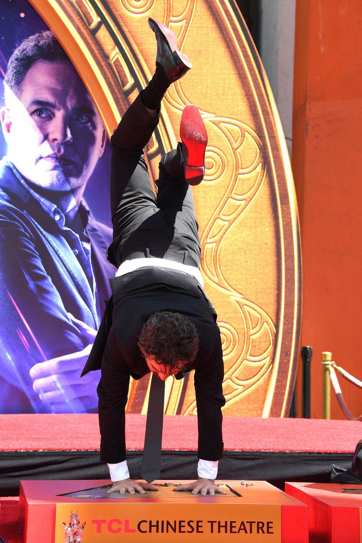 """Der Schauspieler Mark Ruffalo macht seiner Marvel-Figur """"Hulk"""" alle Ehre: Mithilfe eines Kopfstands drückt er seine Handabdrücke kraftvoll in das Zement und reiht sich damit neben hunderte andere Handabdrücke von Stars wieCharlie Chaplin, Frank Sinatra, Clark Gable, Marilyn Monroe oderGeorge Clooney auf dem Vorplatz des historischen Kinos ein."""