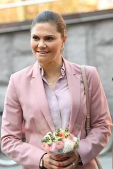 Die Haare trägt sie wie gewohnt geschlossen und ihr dezenter Goldschmuck rundet den Look perfekt ab. Sogar der Blumenstrauß scheint farblich abgestimmt zu sein.