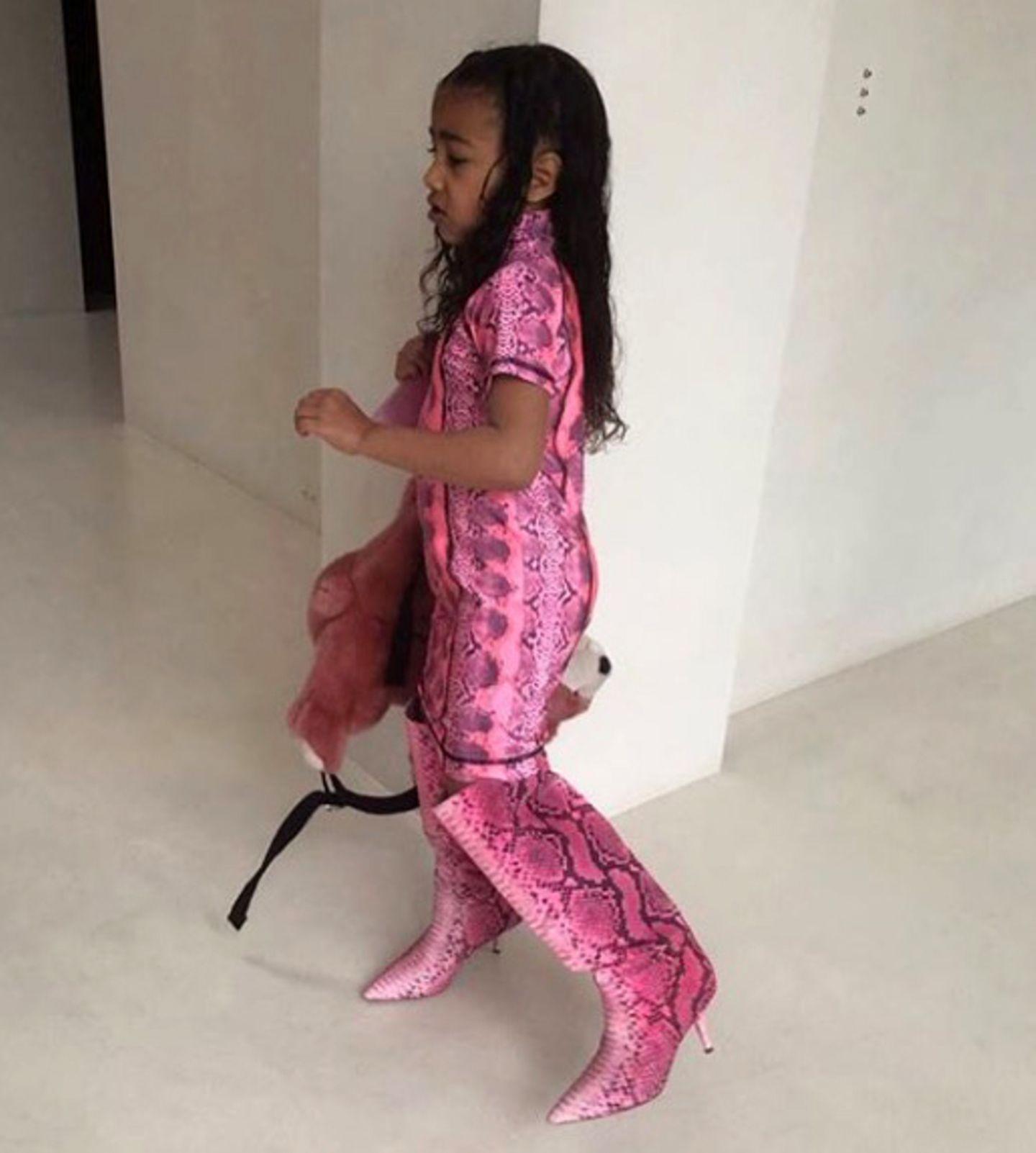 """Denn North West stolziert mit pinkfarbenen Stiefeln der """"Yeezy""""-Kollektion für rund 691 Euro durch die eigenen vier Wände. Doch mit den7,5 Zentimeter hohen Schuhe verkleidet sich die 5-Jährige nicht nur, sie will am liebsten den ganzen Tag in den Boots aus Fake-Schlangenleder verbringen. Mama Kim schiebt dem einen Riegel vor – obgleich sich ihr kleiner Mode-Spross darüber tierisch aufregt."""