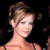 Eine blutjunge Charlize Theron macht 1996 ihre ersten, noch unsicheren Schritte im Filmbusiness. Entsprechend der damaligen Mode trägt sie blauen Lidschatten und hauchdünne Strichaugenbrauen.
