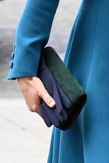 In ihrer rechten Hand hält Kate eine Clutch von Emmy London in grünem Wildleder, die perfekt zu ihren Pumps passt. Auch dunkelblaue Handschuhe hat die Herzogin dabei, die sie ebenfalls elegant in die Kirche trägt.