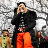 Dieser Look ist wild! Mit derben Boots, knallorangener Hose und Kitty-Mütze heizt Madonna bei einem Konzert dem Publikum ein.