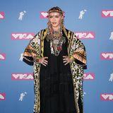 Weniger ist mehr? Das gilt nicht für Madonna! Der Weltstar gibt alles und zeigtsich bei den MTV Video Music Awards in einem bunten Ethno-Look. Zahlreiche Armreifen, Ringe, Ketten und eine Krone schmücken die Sängerin und machen sie auf dem Red Carpet unübersehbar.