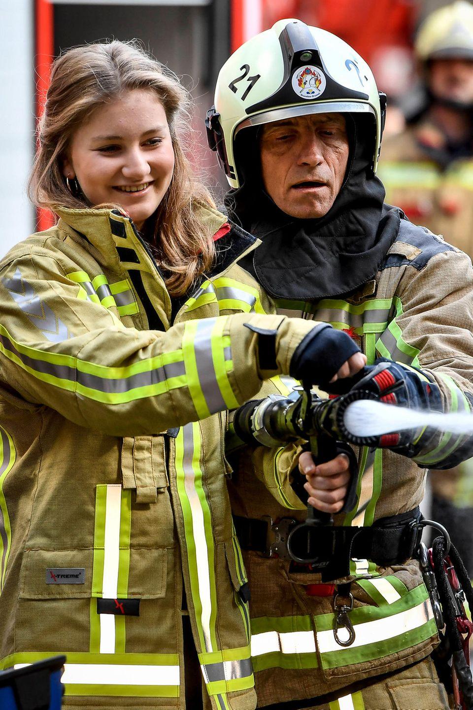 26. April 2019  Prinzessin Elisabeth besuchtmit ihrem Vater König Philippe das Ausbildungszentrumder Brüsseler Feuerwehr. In voller Montur und mit einemWasserschlauch bewaffnethilft sie einem Feuerwehrmann bei Löscharbeiten.