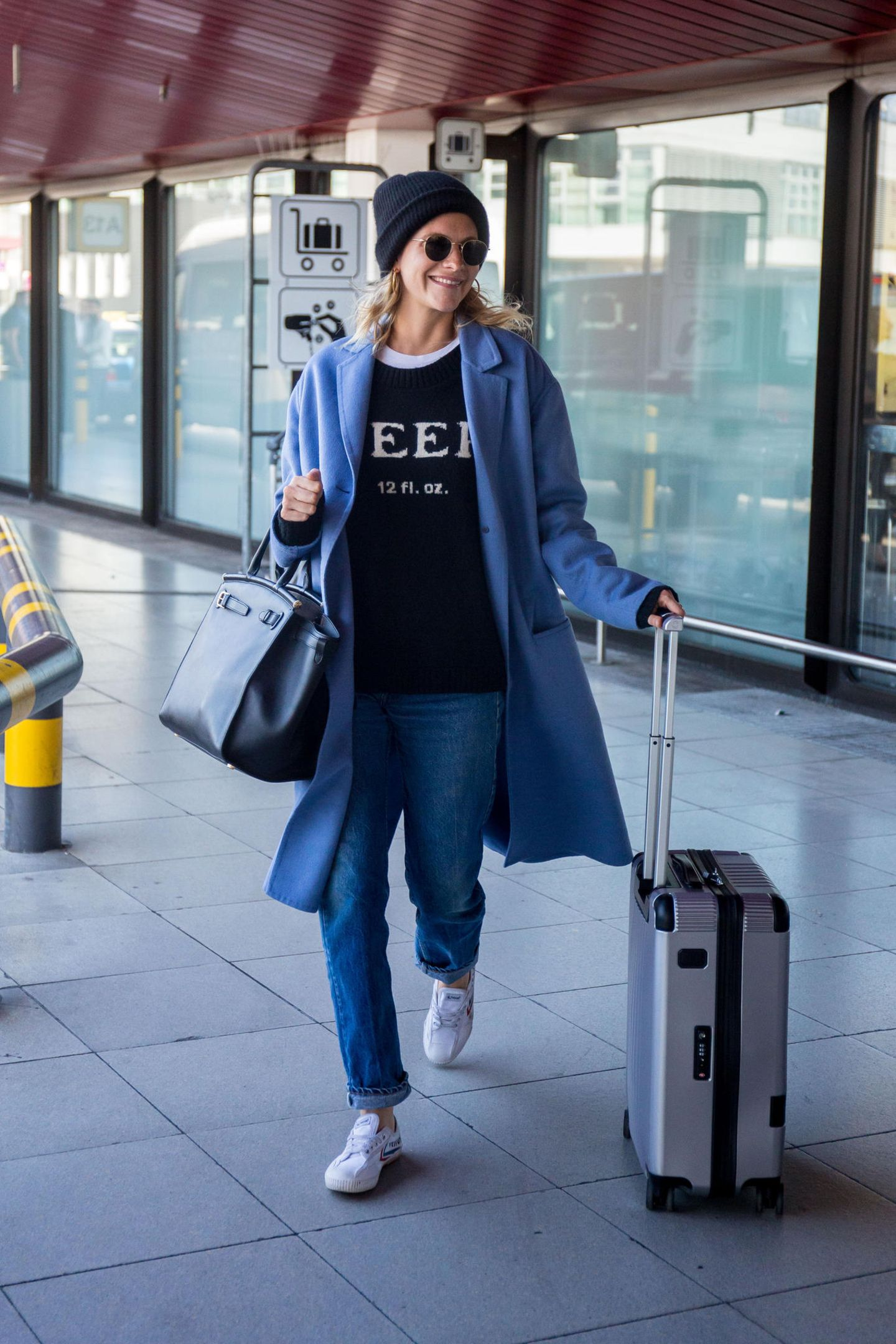 SchauspielerinPoppy Delevingne ist in Berlin angekommen. Das britische Model läuft den Fotografen mit einem strahlenden Lachen entgegen. Dabei trägt sie eine Jeans, ein gemütliches Sweatshirt und einen besonders schönen blauen Mantel.