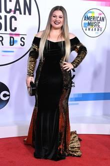 Auf den American Music Awards 2017 erscheint Sängerin Kelly Clarkson in einem schwarzen, figurbetonten Samt-Kleid. Die seitlichen Gold-Verzierungen betonen die Rundungen der 37-Jährigen. Anderthalb Jahre später ...