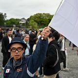 Ein Fan schwenkt die japanische Flagge. Der große rote Punkt stellt die Sonne dar,Weiß ist ein Symbol fürEhrlichkeit und Reinheit.