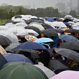 Die Schaulustigen haben sich mit Regenschirmen gegen das nasse Wettergewappnet.