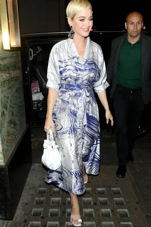 """Katy Perry weiß, wie sie ihre heißen Kurven in Szene setzen kann: Für ein Dinner mit Freunden im Londoner In-Restaurant """"Sexy Fish"""" wählt die Sängerin ein elegantes Wickelkleid in Metallic-Optik, das sich perfekt an ihrenKörper schmiegt."""