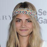 Model Cara Delevingne bändigt ihre wilde Mähne mit einem bunten Haarband im Hippie-Style.
