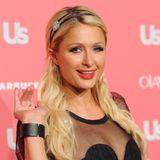 Frisuren mit Haarband sind genau Paris Hiltons Accessoire. Sie trägt die Bänder mal im Hippie-Look oder glamourös wie hier als dünnes Seidenband mit Schmuckdetail.