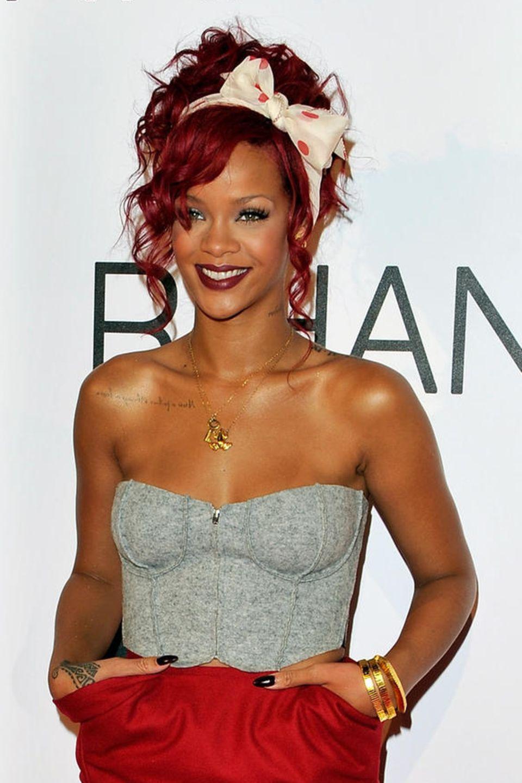 Rihanna hat ein großes Tuch in ihre rote Lockenpracht gebunden und setzt mit der Schleife ein Statement.Dieserockige Variante des Haarbands eignet sich auch für wilde Partynächte.