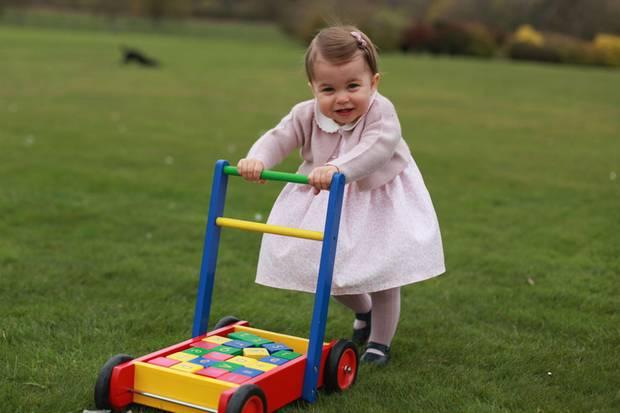 Die einjährige Prinzessin Charlotte übt im Garten mit einem Lauflernwagen.