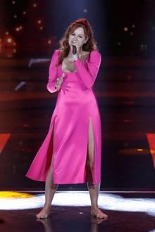 Auf der Bühne wird es dann wieder farbenfroher: In einem pinken Kleid mit hohen Beinschlitzen und ohne Schuhe performt sie für die Zuschauer. Ihre tolle Figur wird von dem fließenden Stoff und dem betonten Schnitt toll in Szene gesetzt.