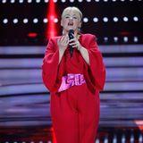 Für ihre Performance wechselt sie in einen knallroten Jumpsuit mit Trapezärmeln, den sie zusätzlich mit einem pink-glänzenden Gürtel aufpeppt.