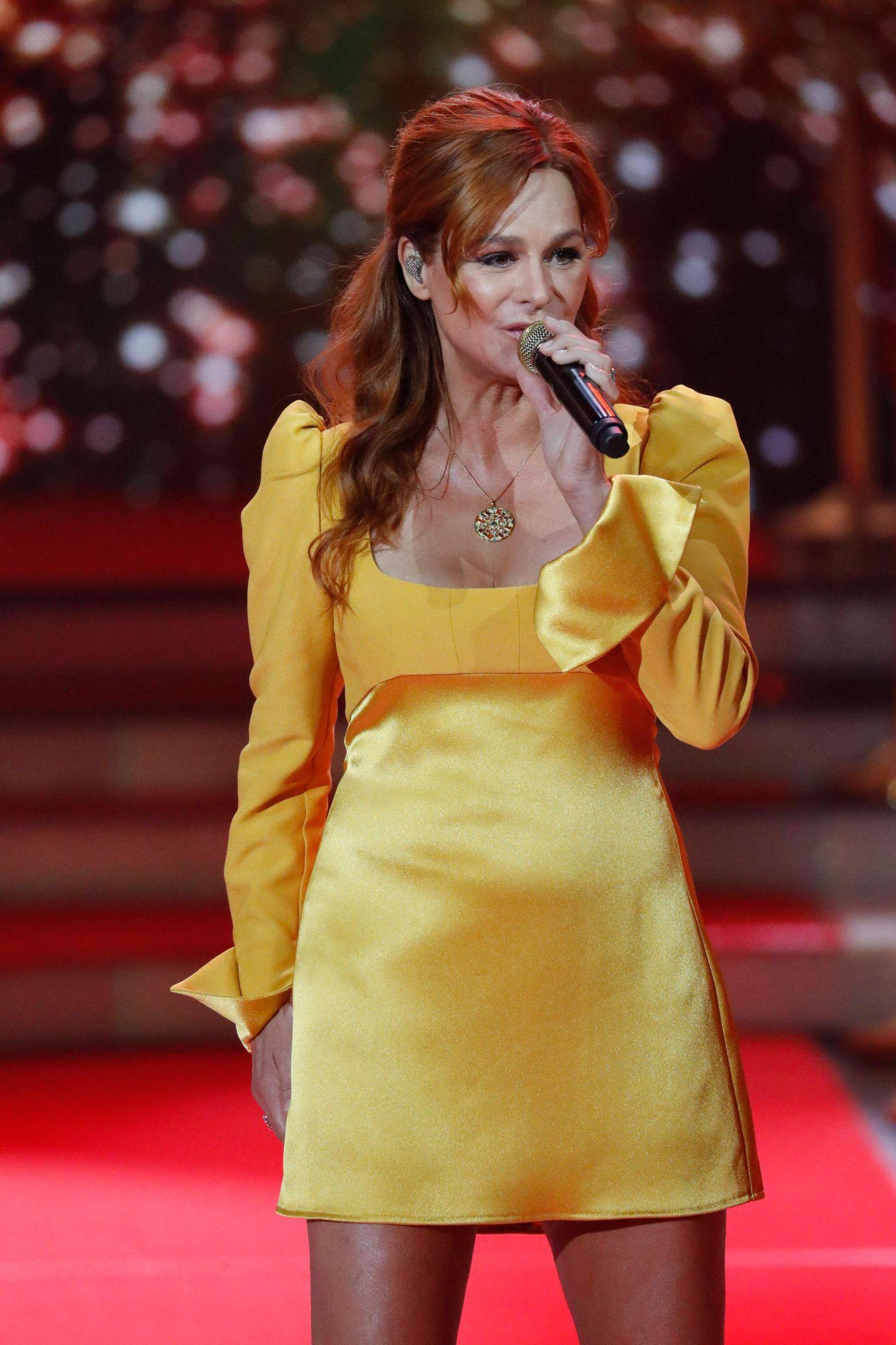 Später wechselt sie in ein kurzes gelbes Dress mit gepufften Ärmeln.