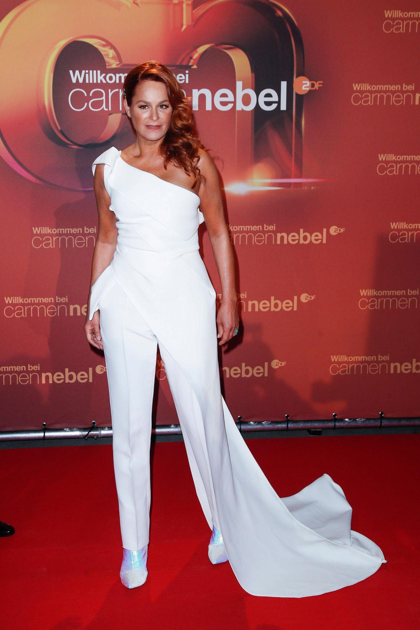 """Andrea Berg zeigt sich auf dem Red Carpet der """"Willkommen bei Carmen Nebel""""-Show in einem weißen Jumpsuit mit One-Shoulder-Ausschnitt und Schleppe. Ihr gebräunter Teint kommt in diesem Outfit besonders gut zur Geltung."""