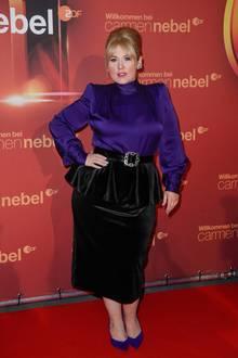 """Maite Kelly setzt auf dem roten Teppich der """"Willkommen bei Carmen Nebel""""-Show auf eine lila Seidenbluse und einen schwarzen Bleistiftrock. Ein auffälliger Gürtel und Schößchen betonen ihre Taille. Dazu hat sie ihr Haar hochtoupiert und trägt knallrote Lippen."""