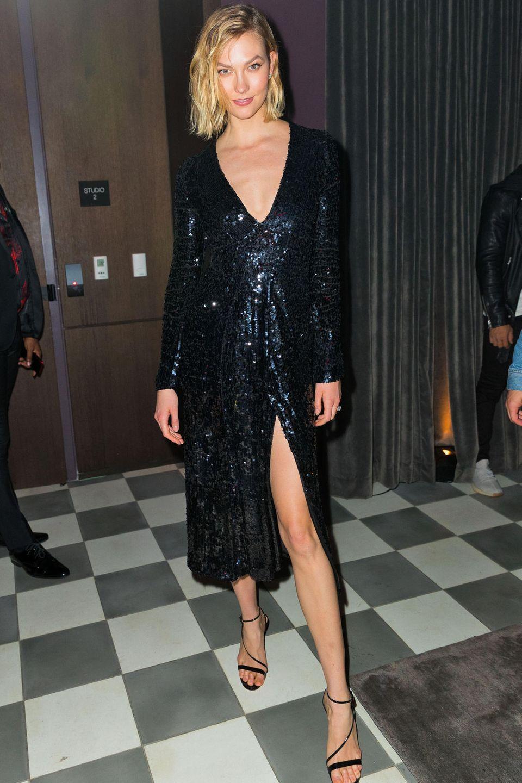 Karlie Kloss strahlt ein einem edlen Glitzer-Kleid von Galvan London. Durch denhohenBeinschlitz und die High-Heels von Gianvito Rossi werdendie tollen Beine der Laufstegschönheit perfekt in Szene gesetzt.