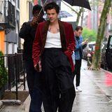 Stylisch trotz Regen: Harry Styles ist auf dem Weg zum Dinner von Anna Wintour. Am Abend vor der großen Gala kombiniertder Sänger ein weinrotes Sakko aus Samt mit einem tief ausgeschnitten Tanktop und einer lässigen, weiten Hose.
