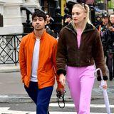 Dieser Date-Look hat es in sich! Joe Jonas und Sophie Turner lassen sich vom New Yorker Regenwetter nicht abschrecken und spazieren in bunten Outfits durch die Stadt. Dabei sind sie zusammen in Pink und Orange richtig modern unterwegs, denn Color-Blocking ist ja wieder total angesagt.