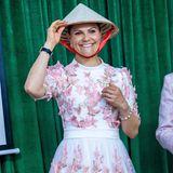 Kronprinzessin Victoria probiert einen traditionellen asiatischen Kegelhut an.